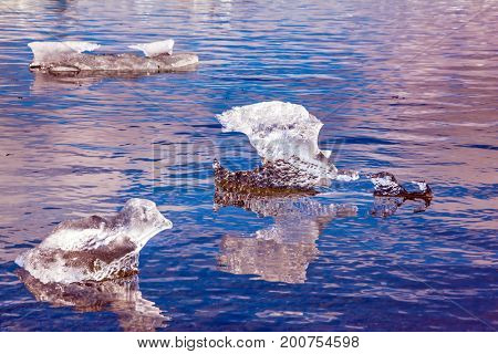Ice floes are reflected in the smooth water surface. The concept of extreme northern tourism. Morning in the Ice Lagoon. Drift ice Ice Lagoon - Jokulsarlon