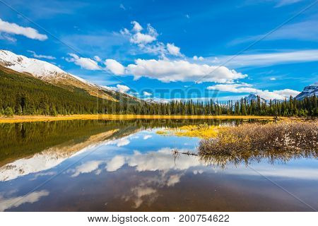 The concept of active tourism and ecotourism. Sky and clouds reflected in the smooth water in the lake. Rocky Mountains on a sunny day