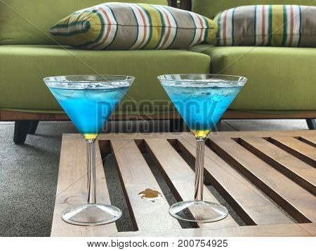 Blue and yellow cocktails in martini glasses on coffee table and green sofa with strippes cushion