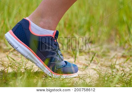 Girl is engaged in cardio runs through forest in sneakers, only legs are visible, legs and sneakers.