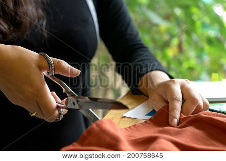 Young Fashion Designer Work With Fabric Cloth On The Wood Table