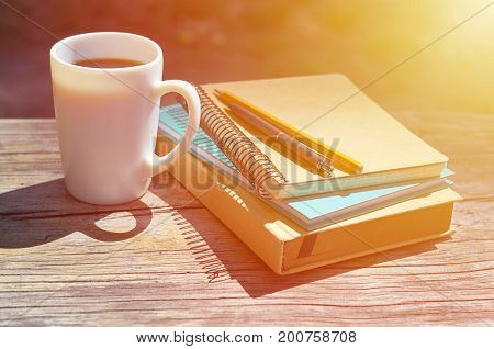 a cup of coffee on a park bench. Notebooks for writing and books. Studies, work and business concept.