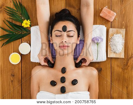 Black marble stone massage in spa, top view. Female patient in wellness center. Professional massagist make relaxation procedure to beautiful indian girl in beauty parlor