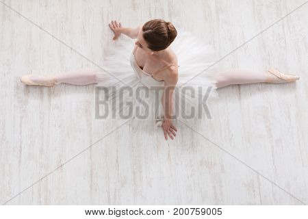 Beautiful graceful ballerina in pointe shoes at white wooden floor makes ballet leg stretching. Ballet practice of classical dancer doing splits, copy space