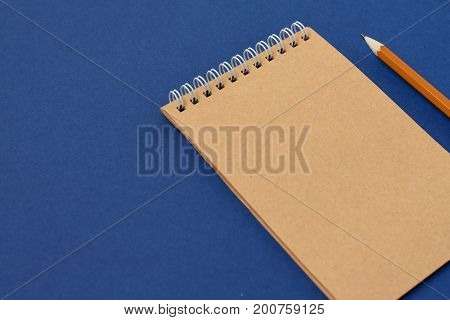 Top view of open spiral blank notebook with pencil on blue paper background. Open vintage notebook. Empty notebook paper for text with  pencil . office concept top view.Copy space. Space for text