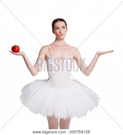 Graceful angry ballerina holding red apple in one hand showing other hand empty, isolated on white. Slimming and weight loss concept, copy space