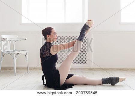 Beautiful graceful ballerina in black leotard practice leg stretching in class room background. Ballet class training, copy space