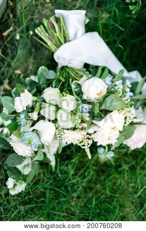 celebration. marriage, spring concept. in the fresh green grass there is bouquet of bride composed of elegant roses and marvelous carnations in traditional white colour