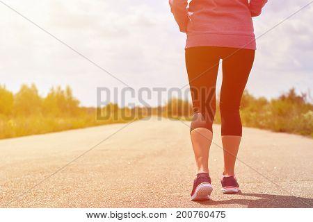 girl in pink hoodie is practicing cardio run in woods, toned image.