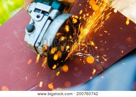 metal sawing with electric angle grinder close up