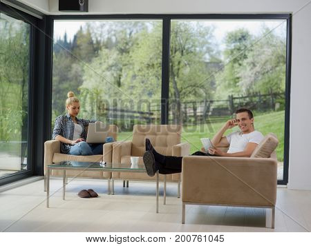 Young couple relaxing at luxurious home with tablet and laptop computers reading in the living room on the sofa couch.