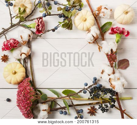 Autumn composition background. Frame made of dried fall flowers, pumpkins, branches and autumn leaves, also cotton, clove and sloe. Top view on white wood, flat lay, copy space