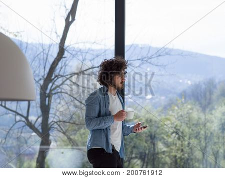 Handsome casual young man drinking coffee and using a mobile phone at  home