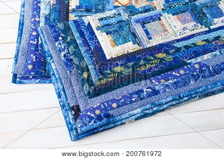decoration, comfort, passion, fondness, stitching, patchwork concept - two dark blue quilt neatly maded of different patches with interesting floral pattern and almost invisible stitches
