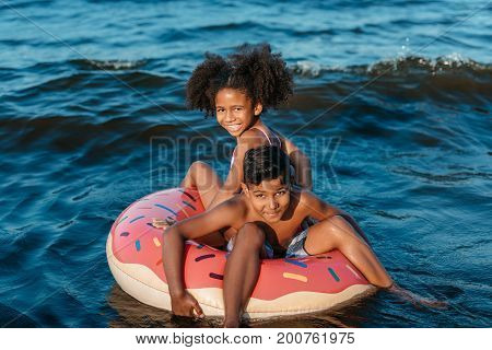 African American Siblings On Swimming Tube