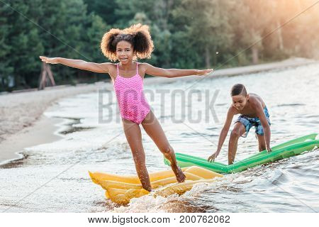 Siblings With Swimming Mattresses At Seaside