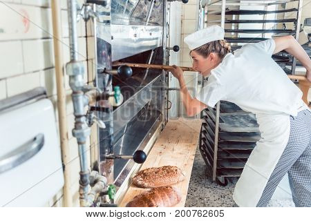 Baker woman getting bread out of bakery oven in her bakery