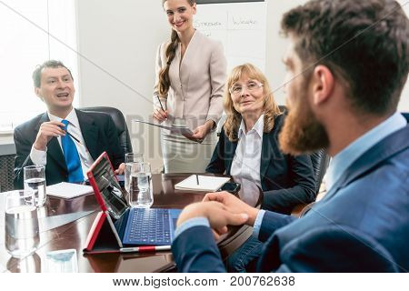 Happy middle-aged managers listening to their younger colleague while planning business in the conference room of a successful corporation