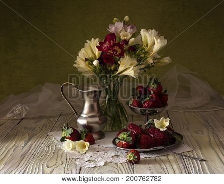 Rural still life with spring freesia and strawberries on a wooden table close-up