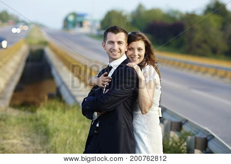 Happy bride and groom laughing smiling on the road on a wedding day.