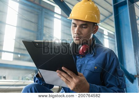 Determined Asian worker writing observations about the manufacturing process indoors