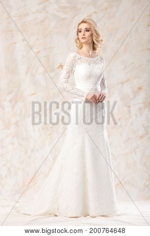 young dreamy lady in wedding festive dress standing indoors on light background, slender pretty woman posing