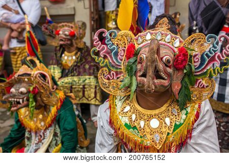 Unidentified balinese people performing in traditional masks during Galungan celebration in Ubud, Bali