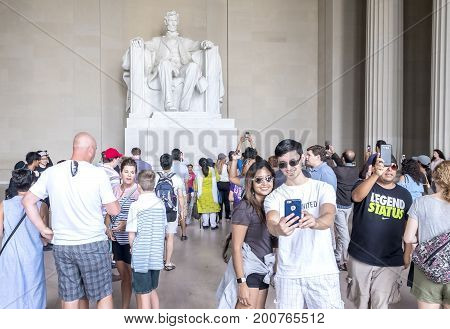 Washington DC, United States of America - August 5, 2017: Inside the Lincoln Memorial Monument, Crowds of People making photographs and selfies in front of the Statue