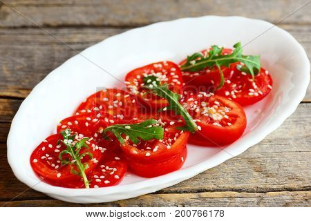 Salad with sliced tomato, rucola, sesame seeds. Quick tomato salad on a white plate isolated on an old wooden background. Sliced tomato salad recipe. Closeup