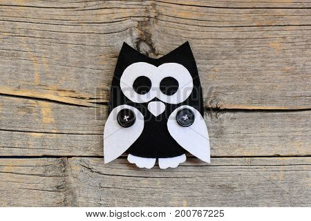 Stuffed felt owl ornament isolated on an old wooden background with empty copy space. DIY sewing crafts from felt. Owl crafts concept for children. Closeup