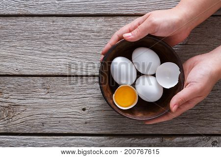 Hands holding fresh chicken white home eggs with cracked eggshell and yolk in bowl at rustic wood table. Top view with copy space. Rural still life, natural healthy food and organic farming concept.