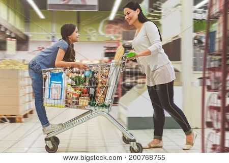 Joyous small girl is playing with product cart her mother pushing forward. They smilingly looking at each other. Focus on happy mom and daughter