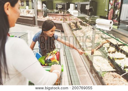 I want this. Joyful little girl is pointing at ready made salad locating behind glass while standing afore mother. Focus on small interested daughter. Copy space on right side