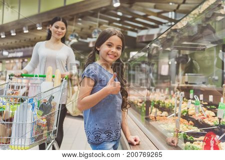 Cheerful small daughter is standing near shop-window and looking at camera with wide smile. Cheery mother locating behind child showing okay sign. Waste up portrait. Low angle