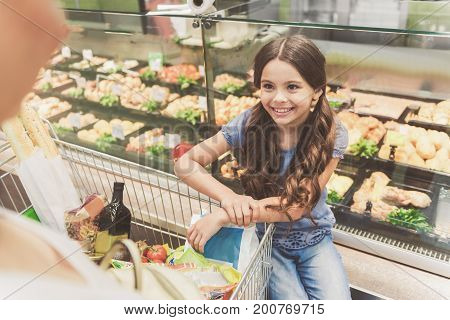 Hilarious little girl is sitting on special shelf near transparent shop-window and looking at adult person with smile. Portrait. Top view