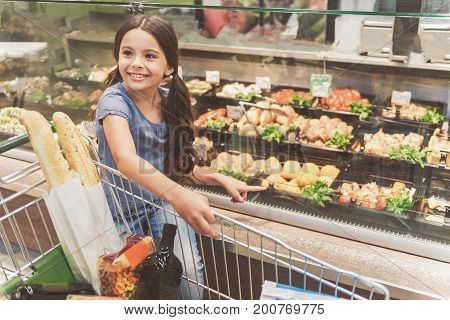 Affable small lady is standing near clear showcase and looking aside with smile. She pointing at chosen kind of food. Portrait. Copy space on right side