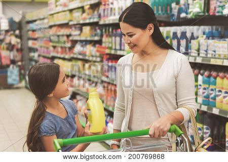 Joyous smiling girl is showing chosen detergent to mother. Adult woman pushing product cart and looking at daughter with smile