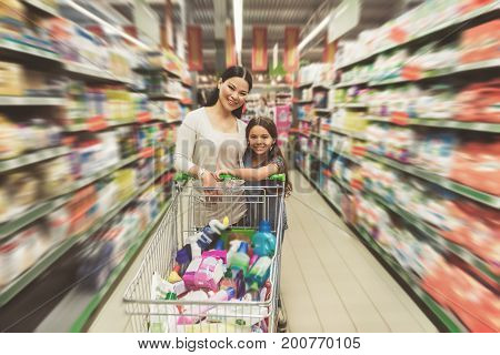 Joyous mother and daughter are standing near product cart full of detergents. They looking at camera with smile. Waist up portrait. Copy space on both sides