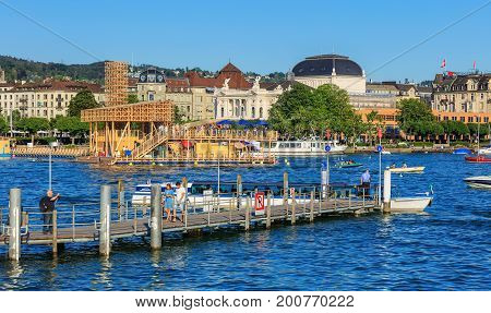 Zurich, Switzerland - 20 July, 2016: people on a pier on Lake Zurich on a summertime evening, buildings of the city of Zurich along the lake. Lake Zurich is a lake in Switzerland, extending southeast of the city of Zurich.