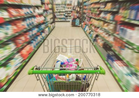 Big product cart is full of various detergents locating between two high shelves in supermarket. Focus on truck. Top view. Copy space