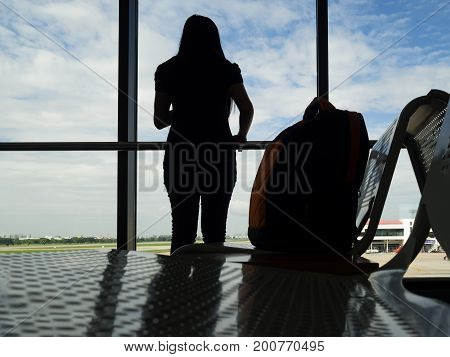 Silhouette woman stand and look outside window with bag on chair waiting flight in airport. Woman travel alone.