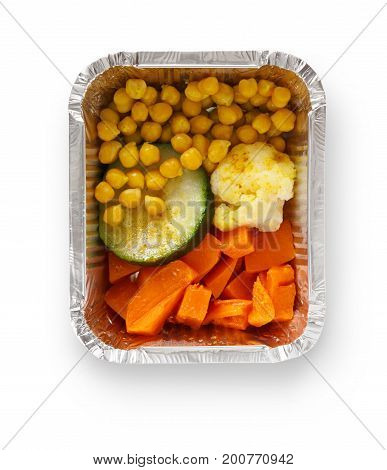 Healthy lunch in foil container. Healthy food take away and delivery. Corn, pumpkin, zuccini, cauliflower in box on white background, closeup, isolated