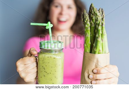 Healthy green smoothie with asparagus in woman's hand. Vegan, raw food, detox and diet lifestyle