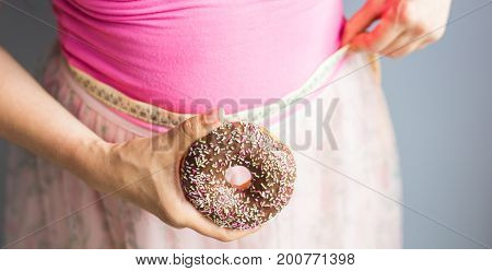 Woman holding donut in hand and check out his body fat with measuring tape.