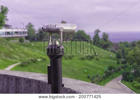 Coin-operated spy viewing machine on nature background