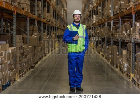 Warehouse worker standing between rows with merchandise and looking at camera