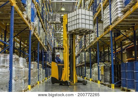 Warehouse worker on stacker taking cargo from rack