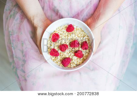 Woman's hands hold healthy and natural breakfast, oatmeal and raspberries in a bowl.