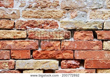 Detail image of a weathered red brick wall.