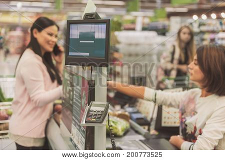 Female buyer is going to make payment for chosen goods. Cashier is sitting at workplace. Focus on monitor of necessary cash machine